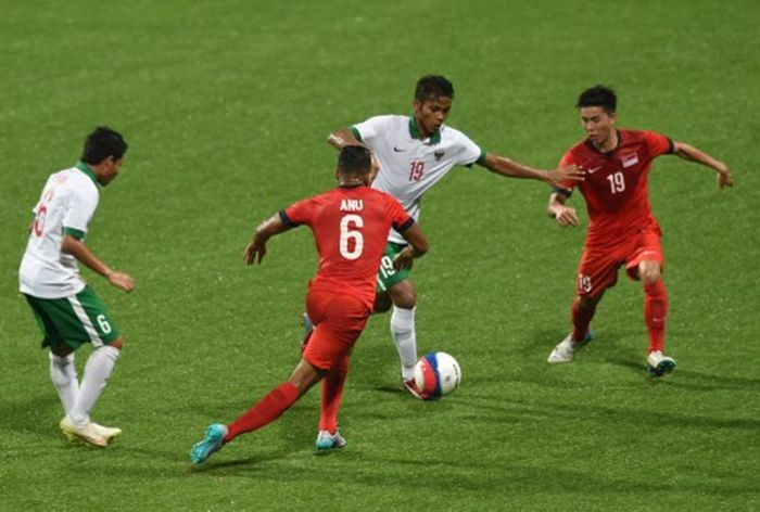 Indonesias midfielder Zulfiandi Zulfiandi (2nd R) dribbles the ball past Singapore players Anumanthan Mohan Kumar (2nd at L) and Stanely Ng Yong Woo in their football first round group A match at the 28th Southeast Asian Games (SEA Games) in Singapore on June 11, 2015. AFP PHOTO / ROSLAN RAHMAN / AFP PHOTO / ROSLAN RAHMAN