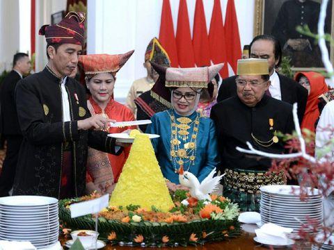 Jokowi sedang memotong nasi tumpeng.