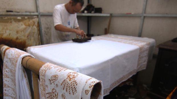 Seorang perajin mencetak kain <a href='https://uzone.id/tag/batik' alt='batik' title='batik'>batik</a> khas Betawi menggunakan malam atau lilin yang dipanaskan di kawasan Terogong, Cilandak, Jakarta.