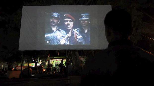 Warga nonton bareng (nobar) pemutaran film pengkhianatan G30S/PKI di Lapangan Hiraq Lhokseumawe, Aceh (23/9) malam. Nobar pengkhianatan G30S/PKI yang diperintahkan Panglima TNI kepada jajaran TNI diseluruh daerah di Indonesia itu bertujuan mengingatkan kembali sejarah peristiwa pemberontakan PKI terhadap NKRI pada 30 September 1965, sekaligus kemanunggalan TNI dengan rakyat meningkatkan kewaspadaan terhadap bahaya laten komunisme serta menumbuhkan rasa nasionalisme dan cinta Tanah Air. ANTARA FOTO/Rahmad/pd/17.