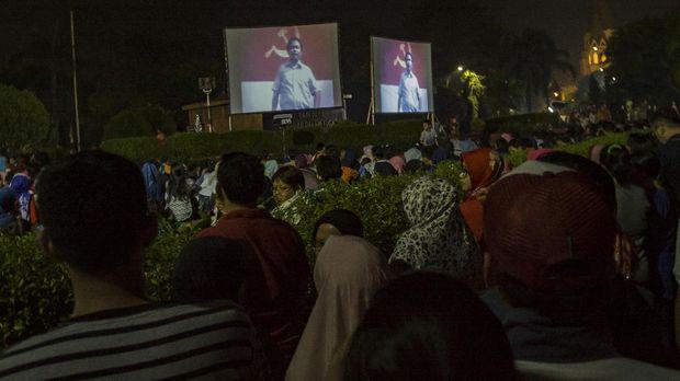 Warga menyaksikan film pengkhianatan G30S/PKI pada acara nonton bareng di Bundaran Mall Graha Cijantung, Jakarta, Sabtu (23/9). Kopassus mengadakan nonton bareng film pengkhianatan G30S/PKI untuk mengingatkan kembali sejarah pemberontakan PKI terhadap NKRI yang ingin merubah ideologi Pancasila menjadi paham komunis dan memberikan pemahaman kepada generasi muda tentang bahaya laten komunis. ANTARA FOTO/Galih Pradipta/pd/17