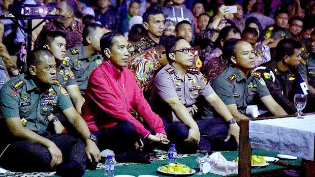 Presiden Joko Widodo (kedua kiri) didampingi Gatot Nurmantyo, yang saat itu masih menjabat Panglima TNI (kiri), menonton film G30S/PKI, di lapangan tenis indoor Markas Korem 061 Suryakencana Bogor, Jawa Barat, Jumat (29/9) malam.