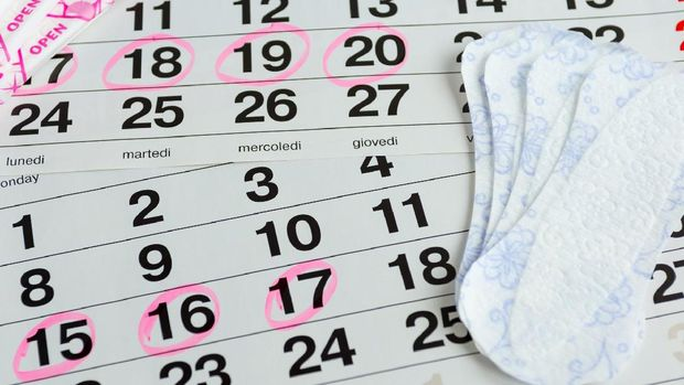 Woman protecting health , menstruation days , laying on a calendar with the selected days