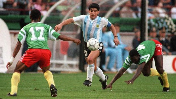Argentinian forward Diego Maradona juggles with the ball as he runs past Cameroon's Benjamin Massing during the World Cup opening soccer match between Cameroon and Argentina 08 June 1990 in Milan. Cameroon upset the defending world champions 1-0.  (At left is Victor Ndip Akem)  AFP PHOTO/DANIEL GARCIA / AFP PHOTO / DANIEL GARCIA