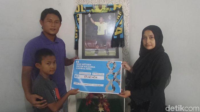 Istri alm. Choirul Huda, Lidya Anggraini, menerima donasi dari netizen yang dihimpun Ernest Prakasa.  (Eko Sudjarwo/detikSport)