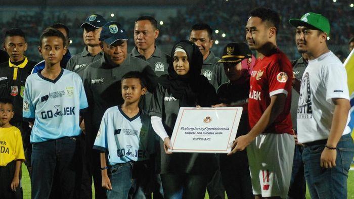 Ponaryo Astaman (kedua kanan) menyerahkan hasil lelang jersey kiper kepada Lidya Agraeni (tengah), istri almarhum kiper Persela Choirul Huda (Syaiful Arif/Antara Foto)