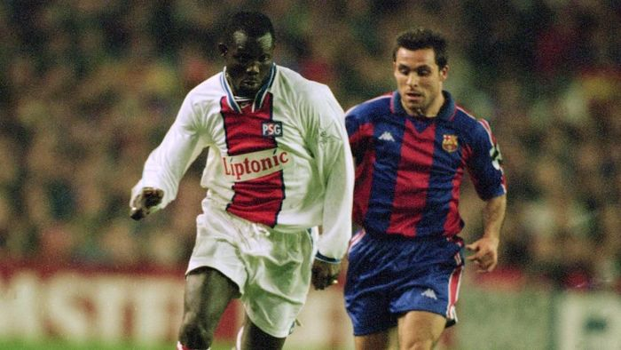 George Weah of Paris St Germain and Sergi of Barcelona BARCELONA - MARCH 1: George Weah of Paris St Germain charges past Sergi of Barcelona during the European Cup quarter final first leg match held on March 1, 1995 at the Nou Camp, in Barcelona, Spain. The match ended in a 1-1 draw. (Photo by Clive Mason/Getty Images)