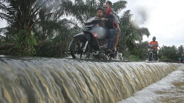 Warga melintasi banjir di Desa Lhok Sentang, Julok, Aceh Timur, Aceh, Selasa (5/12). Tingginya curah hujan sejak dua pekan terakhir membuat sungai Arakundo meluap dan merendam ratusan rumah warga serta ratusan hektar lahan pertanian, tambak ikan warga, perkebunan dengan ketinggian air 50 sampai 150 cm. ANTARA FOTO/Syifa Yulinnas/foc/17.