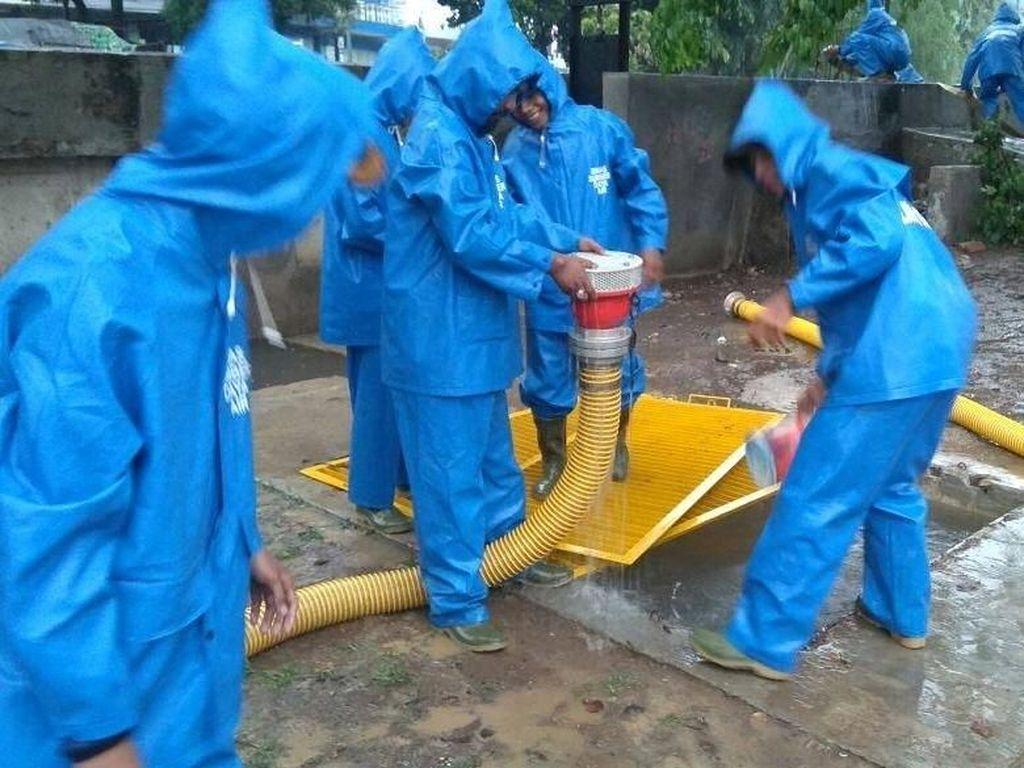 Foto: Aksi Pasukan Biru Sedot Genangan di Tengah Hujan Deras
