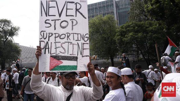Massa Aksi Bela Palestina atau aksi 1712 terus berdatangan ke Monas, Jakarta Pusat. Mereka membawa atribut berupa bendera dan spanduk berisikan dukungan untuk Palestina.Jakarta.Minggu 17 Desember 2017.CNN Indonesia/Andry Novelino