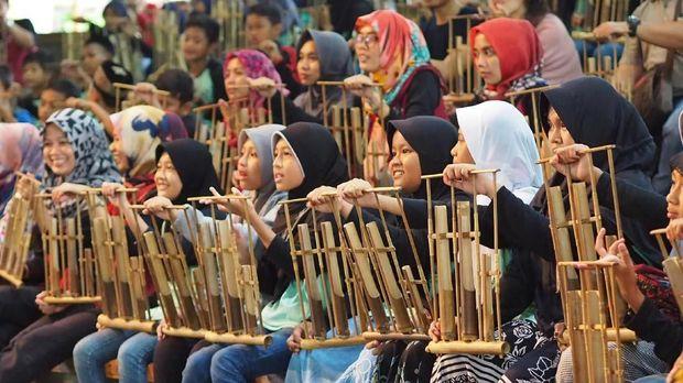BANDUNG, INDONESIA – 3 JANUARI: Para pengunjung diajari memainkan angklung, sebuah instrumen tradisional dari Indonesia, di Saung Angklung Udjo yang terletak di Bandung, Indonesia pada 3 Januari 2017. Pada tahun 2010, UNESCO secara resmi mengakui angklung sebagai Masterpiece of Oral and Intagible Heritage of Humanity.  ( Mahendra Moonstar - Anadolu Agency )