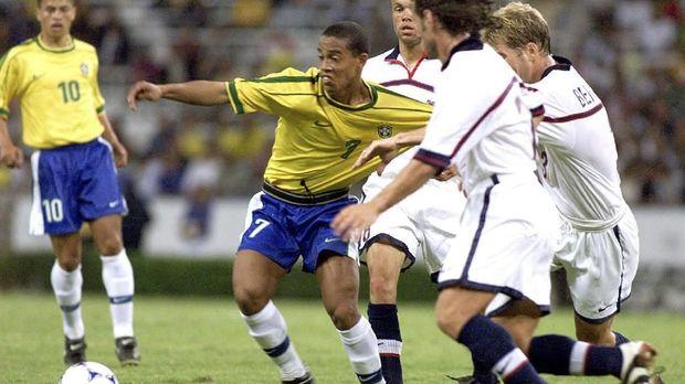 Ronaldinho (C) of Brazil is held by US players during their match 28 July 1999 in Guadalajara.Ronaldinho(C), goleador de la seleccion brasilera, es detenido por jugadores de la seleccion de Estados Unidos en la fase final del partido jugado entre ambas selecciones en Guadalajara, Mexico, 28 de julio de 1999, por la Copa FIFA Confederaciones. Brasil gano 2-0.    (ELECTRONIC IMAGE)    AFP PHOTO/JORGE SILVA / AFP PHOTO / JORGE SILVA
