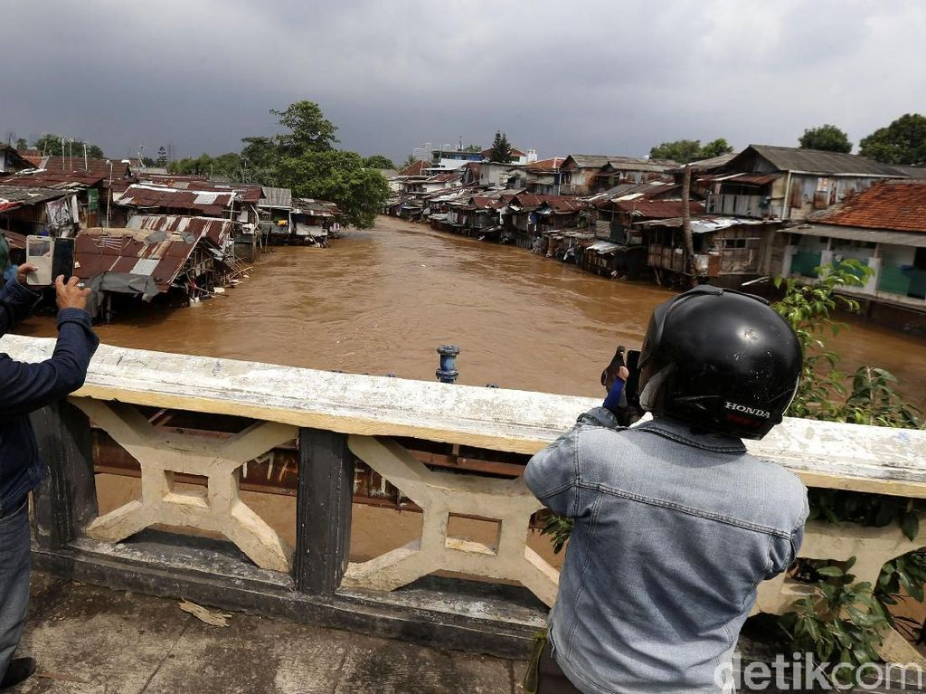 Foto: Warga Menonton Aliran Sungai CiIiwung yang Melimpah
