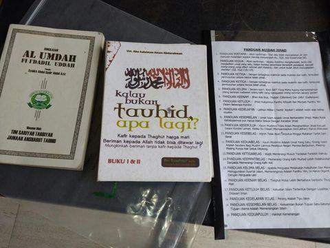 Dua buku dan satu lembar bacaan yang ditemukan polisi di rumah Lutfianto