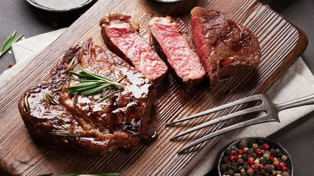 Sliced medium rare grilled Steak Ribeye with french fries on serving board block on wooden background