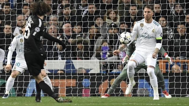 Paris Saint-Germain's French midfielder Adrien Rabiot (L) kicks the ball in front of Real Madrid's Spanish defender Sergio Ramos (R) during the UEFA Champions League round of sixteen first leg football match Real Madrid CF against Paris Saint-Germain (PSG) at the Santiago Bernabeu stadium in Madrid on February 14, 2018.   / AFP PHOTO / GABRIEL BOUYS