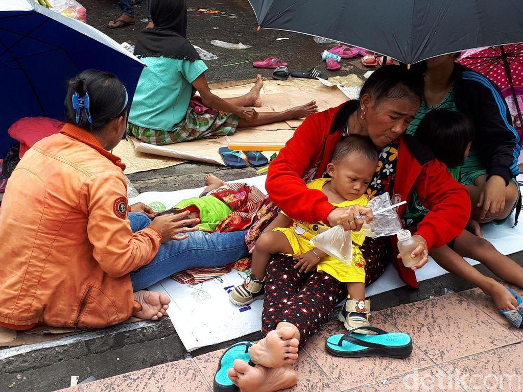 Gendong Anak, Ibu-ibu Berpayung Menanti Angpao di Petak Sembilan
