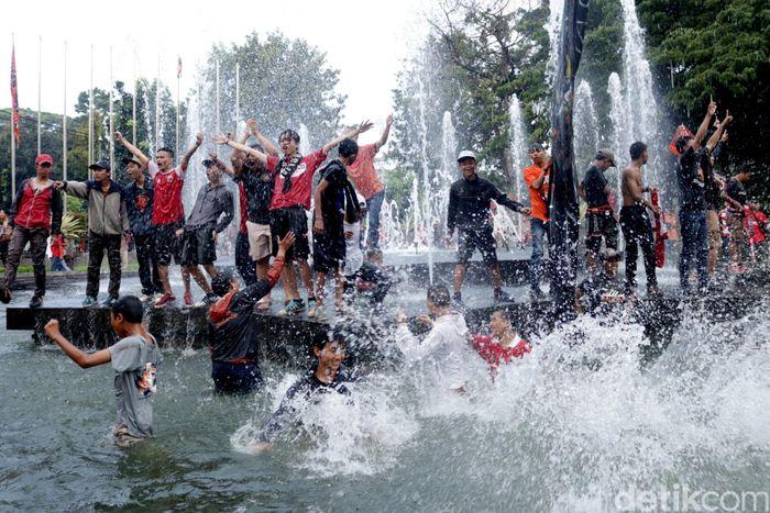 Penampakan sejumlah massa Jakmania yang menceburkan diri ke kolam air mancur di Balai Kota, Jakarta, Minggu (18/2/2018).