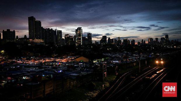 Lapak pedagang pakaian yang telah buka sejak pukul 5 pagi di kawasan Bongkaran Tanah Abang, Jakarta, Senin 19 Februari 2018. Para pedagang biasanya telah sampai di lokasi pada pukul 2 dini hari, dan calon pembeli bisa datang sejak pukul 5 pagi hingga pukul 12 siang. Area yang dipakai adalah lahan parkir untuk kendaraan berat seperti truk yang memang diperuntukkan mengangkut barang-barang dagangan para pedagang di Pasar Tanah Abang. CNNIndonesia/Safir Makki