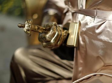 Adalah seniman bernama Plastic Jesus yang membuat dan menaruh patung Harvey yang tengah menggenggam piala Oscar di tangannya. REUTERS/Lucy Nicholson.