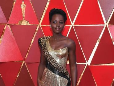 Lupita Nyongo tetap memancarkan pesona dan aura seksi kala tampil dengan gaun warna emas.Kevork Djansezian/Getty Images.