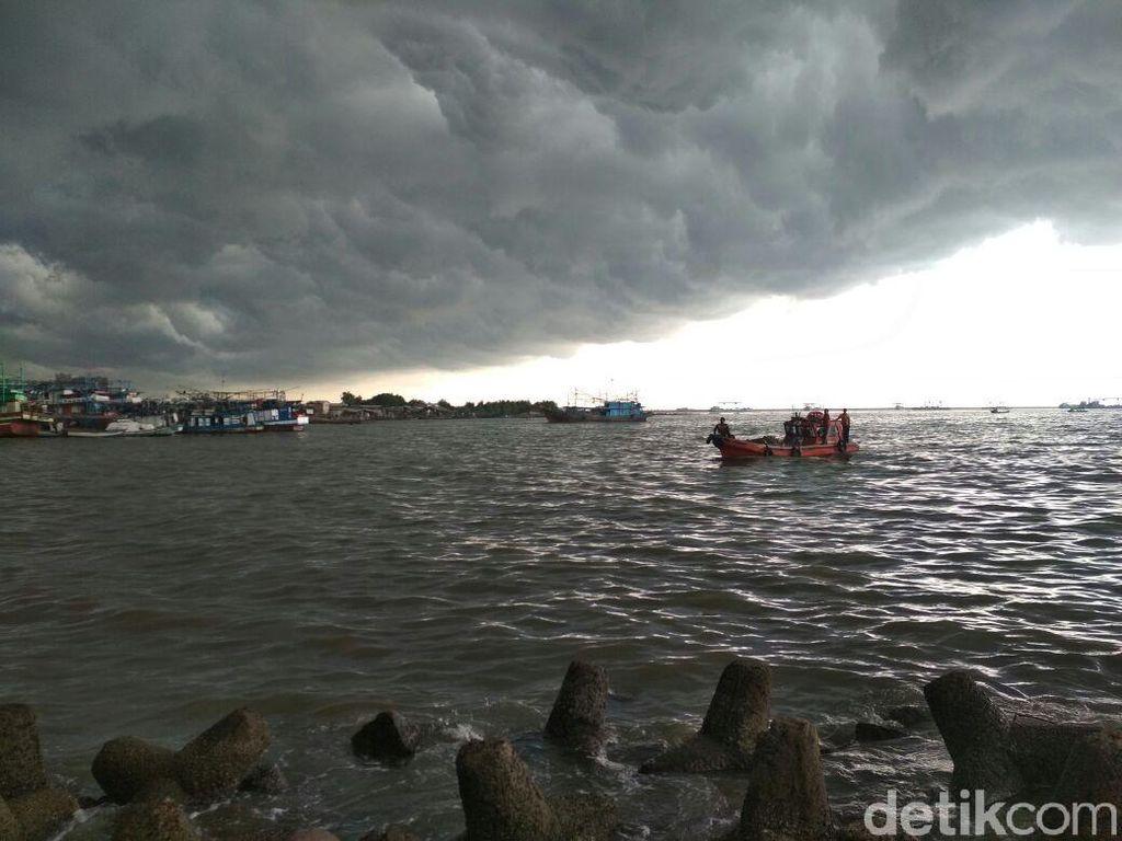 Awan Gelap Payungi Petugas Bersihkan Lautan Sampah di Teluk Jakarta