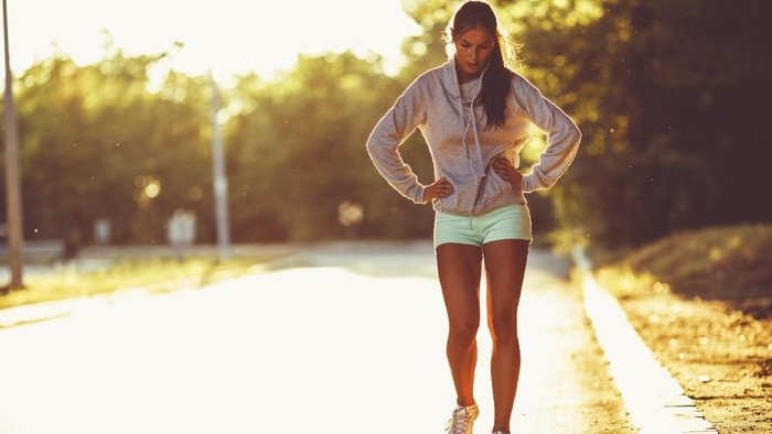 Tired female runner walking.She is exhausted of running.