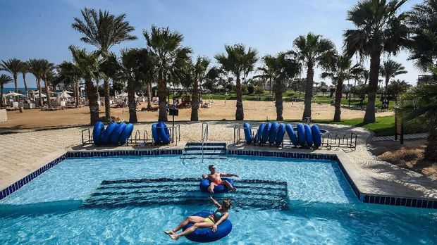 Tourists lie on floats in a pool at a hotel in Egypt's Red Sea resort of Hurghada on February 19, 2018.Egypt is seeing a promising rebound in tourism following devastating jihadist attacks, in welcome news to the government of the president as he seeks re-election this month. / AFP PHOTO / MOHAMED EL-SHAHED