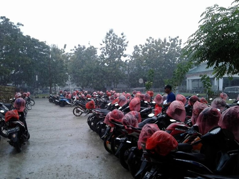 Juru Parkir Baik Hati, Rela Hujan-hujanan demi Bungkus Helm Orang