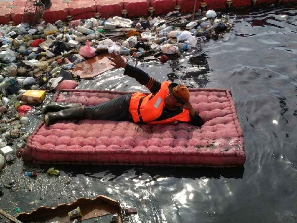 Gaya Petugas Badan Air Tiduran di Kasur yang Dibuang ke Kali