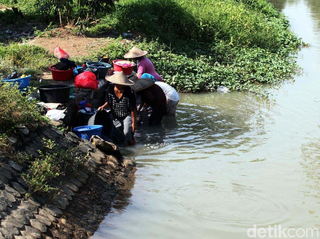 Mencuci Pakaian di Sungai Keruh