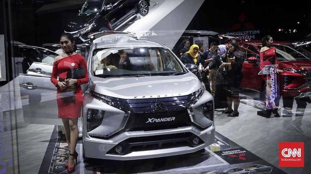 Salah satu penjual Mitsubishi berdiri di samping Xpander di acara IIMS 2018