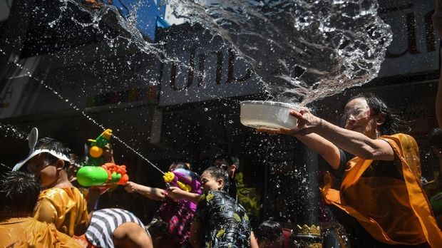 Revellers splash water over each other during a mass water fight as they celebrate Songkran, the Thai New Year, on Silom Road in Bangkok on April 13, 2018. / AFP PHOTO / LILLIAN SUWANRUMPHA