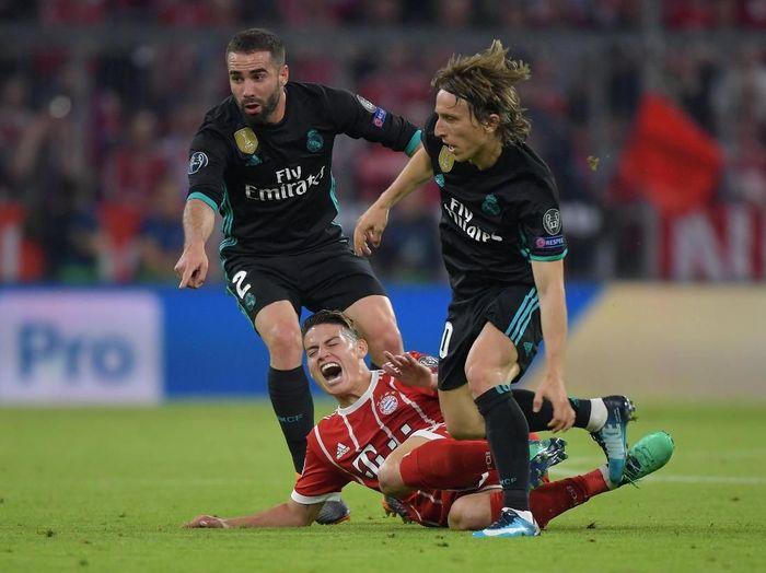 James Rodriguez pun terpaksa harus dihentikan oleh Dani Carvajal dan Luka Modric. (Foto: Thorsten Wagner/Reuters)