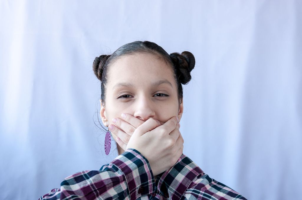 A teenage girl in a plaid shirt covered her mouth with her hands