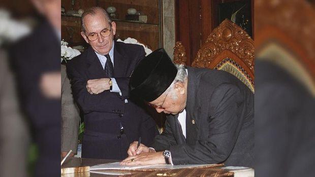 Presiden RI ke-2 Soeharto ketika menandatangani paket bantuan dari IMF pada Oktober 1997.