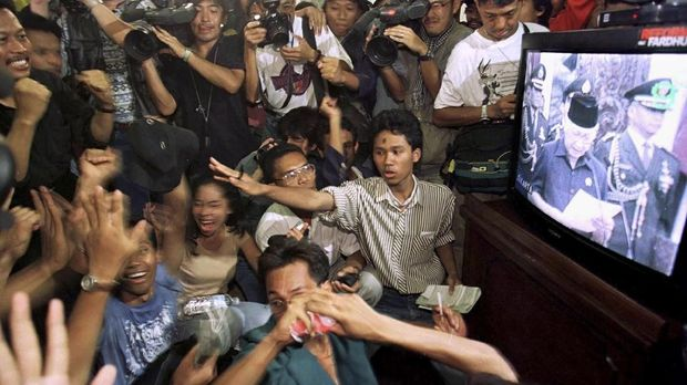 Mahasiswa di gedung DPR/MPR menyaksikan pidato pengunduran diri Soeharto melalui televisi.