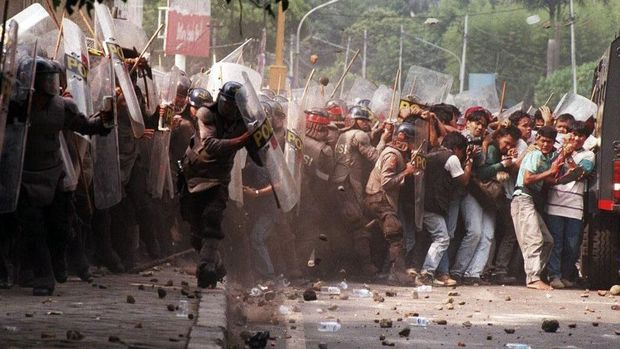 (FILES) Riot police protect themselves from rocks thrown by supporters of ousted Indonesian Democracy Party (PDI) leader Megawati Sukarnoputri 27 July 1996, before violently dispersing a crowd who gathered in central Jakarta after police raided the PDI headquarters. Indonesian security forces 27 July sealed off a central Jakarta district for the first anniversary of deadly riots sparked by storming of the opposition PDI.     AFP PHOTO/FILES/John MACDOUGALL    / AFP PHOTO / JOHN MACDOUGALL