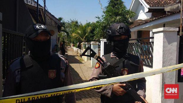Petugas berjaga di lokasi penggrebekan terduga teroris, di Probolinggo, Selasa (22/5).