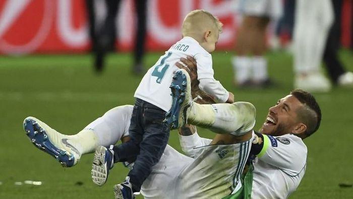 Sergio Ramos, yang disebut sebagai biang ceeranya Mohamad Salah, merayakan trofi Liga Champions bersama putra keduanya, Marco, (Paul Ellis/AFP)