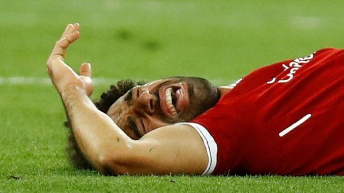 Mohamed Salah kesakitan akibat cedera bahu di final Liga Champions 2018. (Foto: Kai Pfaffenbach/Reuters)