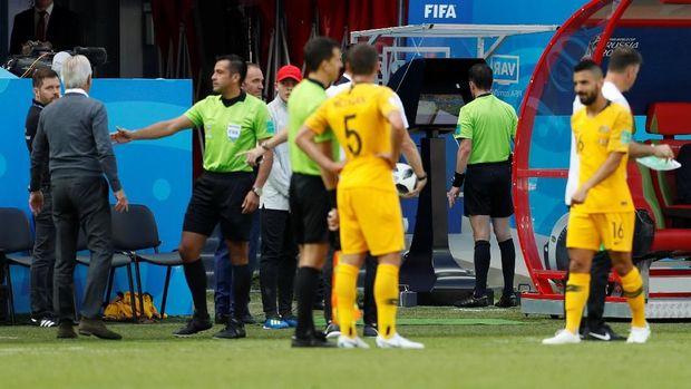 Wasit Andreas Cunha tengah melihat reka ulang adegan dalam laga Prancis lawan Australia.