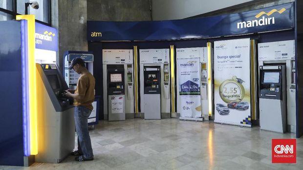 Nasabah melakukan transaksi di mesin Atm cabang Bank Mandiri Gambir pada saat libur lebaran, Jakarta (20/6). Per tanggal 21 Juni 2018, seluruh kantor cabang Bank Mandiri sudah beroperasi secara menyeluruh. (CNN Indonesia/ Hesti Rika)