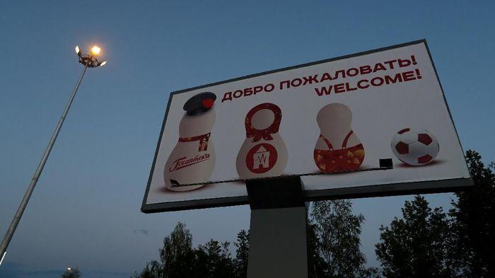 Papan iklan bertuliskan Selamat Datang!, dengan mengsung boneka Matryoshka khas Rusia dan berciri Piala Dunia, terpampang di luar bandara internasional Strigino Nizhny Novgorod. (Foto: Murad Sezer/Reuters)