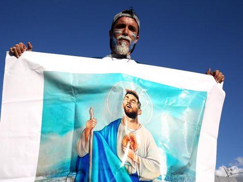 Seorang suporter Argentina membawa poster besar Lionel Messi