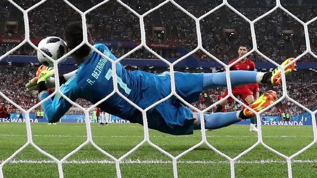 Alireza Beiranvand menepis penalti Cristiano Ronaldo.