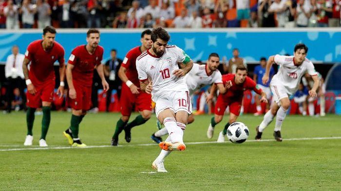 Pemain Iran Karim Ansarifard sukses mengeksekusi penalti ke gawang Portugal (Foto: Matthew Childs/Reuters)