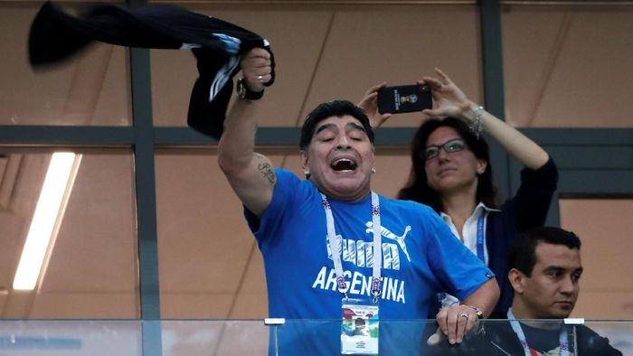 Diego Maradona mendorong fans yang berfoto dengannya (Reuters)