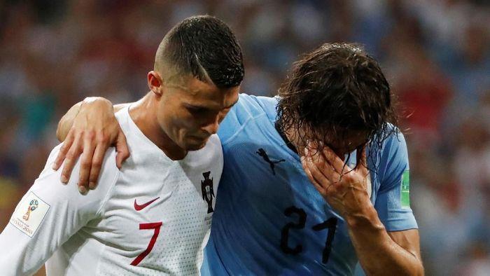 Momen Ronaldo bantu memapah Cavani (Foto: Jorge Silva/Reuters)