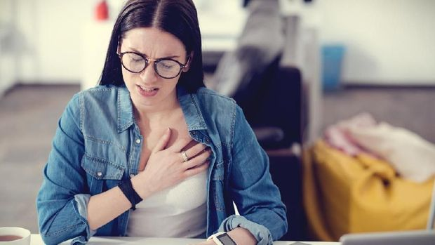 Pain in the chest. Unhappy pleasant young woman sitting at the table and working while feeling unwell
